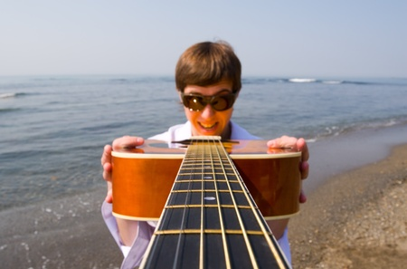 Young man (musician) holds a guitar in hands.Coast. photo