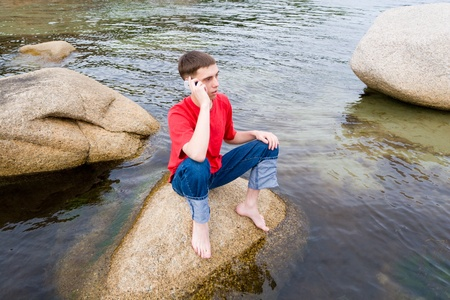 The young man speaks by mobile on a stone at the sea. photo