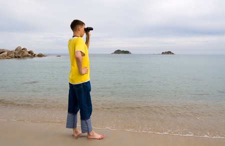 The man stands on a beach and looks in the old binocular. photo