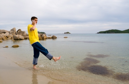 Coast.The young man talks on mobile and does(makes) splashes by a leg(foot). photo