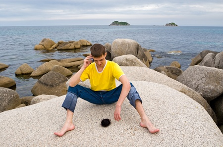 Young man talks on mobile on a deserted beach photo