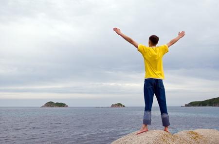 independencia: El joven costs(stands) sobre una piedra en el mar que se extend�a de manos.