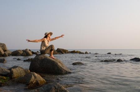 Lady sits on a stone at the sea, meditates. Above horizon white overcast. photo