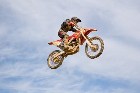 Carreras en motocicletas. El motociclista vuela después de un trampolín sobre un fondo del cielo. Editorial