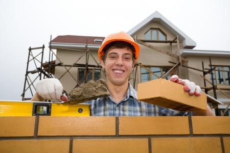 bricklayer: Alba�il sostiene un ladrillo en una mano. Una casa construida.