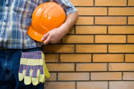 place of work: Mason holds a helmet on a background of a brick wall. Stock Photo
