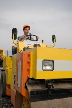 steamroller: Worker operates a steamroller. Stock Photo