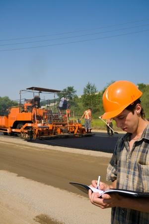 road paving: Inspector de carretera sobre una plataforma de trabajo. Apilamiento de asfalto nuevo. Foto de archivo