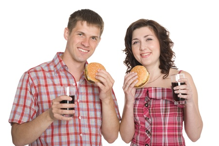 Happy girl and a guy eating hamburgers and drinking a refreshing drink. Isolated on white. photo