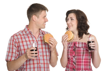 Joyful girl and a guy eating hamburgers and drinking a refreshing drink. Stock Photo - 10551471