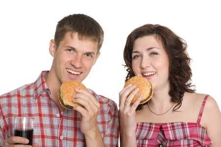 Girl and a guy eating cheeseburgers and drinking a refreshing drink. photo