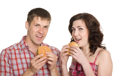 Girl and a guy eating hamburgers Isolated on white. photo