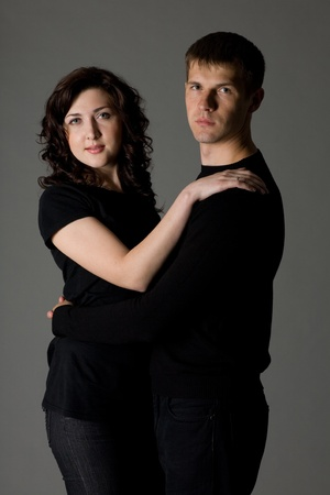 Portrait of a young couple on a gray background. photo