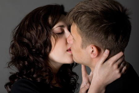 Girl and guy kiss on a gray background. photo