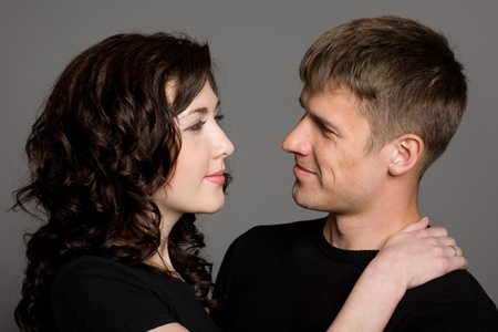 A beautiful smiling young couple on a gray background. photo