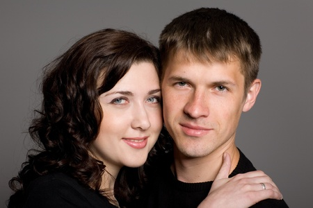 Portrait of a smiling young couple on a gray background. photo