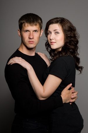 Young beautiful couple in the background of a gray wall. photo