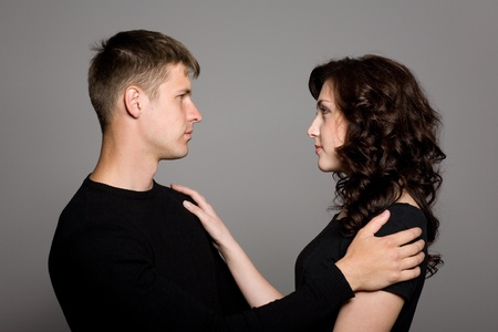 Beautiful young couple on a background of gray walls. photo