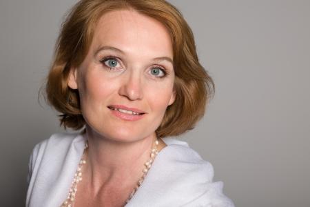 edad media: Sonriente mujer de mediana edad con un fondo gris.