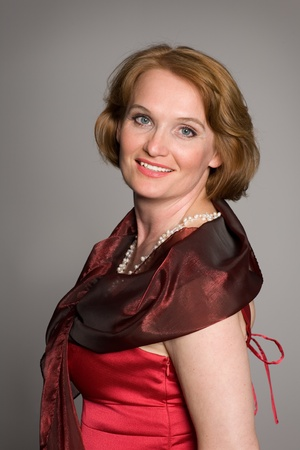 red head woman: Smiling middle aged woman in a red dress.
