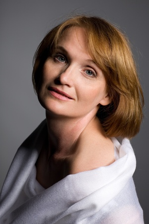 Beautiful mature woman smiling on a gray background. Stock Photo - 10556322