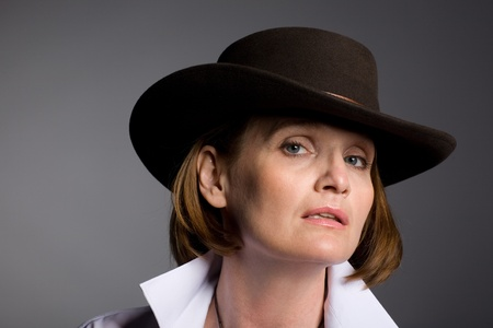 Smiling attractive mature woman in a stetson on a gray background. photo