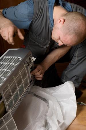 fettler: T�cnico de aire acondicionado prepara un nuevo aire acondicionado para instalarse en el apartamento. Foto de archivo