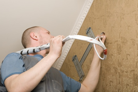 Technician of the air conditioning system is working on installing a new air conditioner in the apartment. Stock Photo