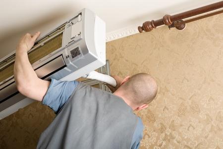aire acondicionado: Maestro de aire acondicionado instala un nuevo aire acondicionado en el apartamento.