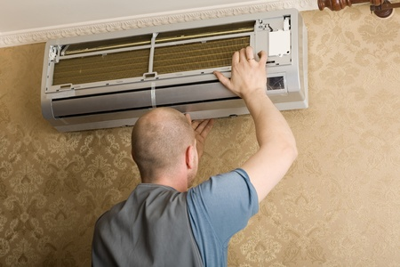 cold air: Air conditioning technician installs a new air conditioner in the apartment. Stock Photo