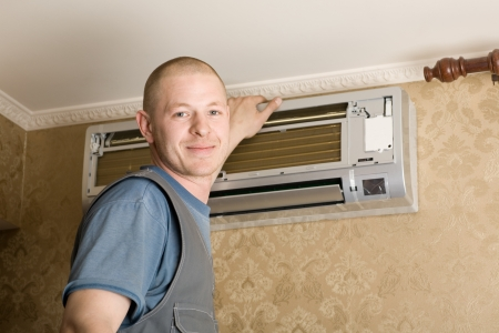 Air conditioning technician installs a new air conditioner in the apartment. Stock Photo