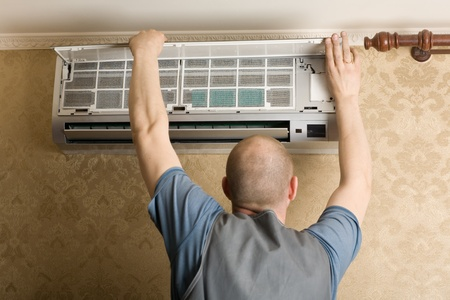 conditioner: Adjuster air conditioning system sets a new air conditioner in the apartment. Stock Photo