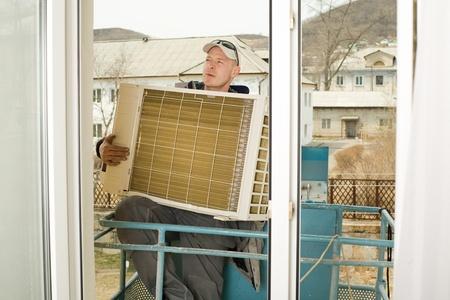 fettler: Sistema de aire acondicionado del regulador establece una nueva unidad externa aire acondicionado. Es maestro en la torre de ascensor fuera de la ventana.