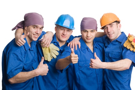 four fingers: A friendly young team of construction workers shows thumbs sign okay.