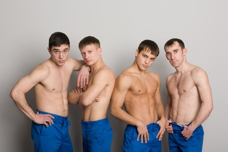 Group of young guys with muscular bodies, naked to the waist.  photo