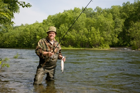 Fisherman caught a salmon(loach) on the river. Primorskiy kray. Russia. Stock Photo - 10556319
