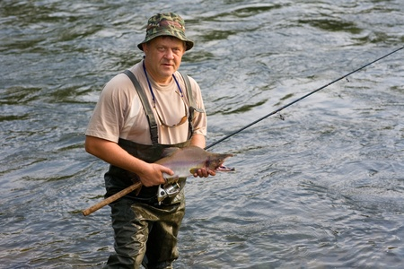 Fisherman caught a salmon (pink salmon) on the River. Early morning. Stock Photo - 10556311
