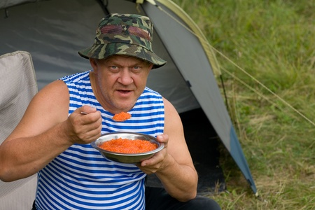 Middle-aged man eating freshly prepared (salted) red caviar in field conditions. Fun ;) Russia. Stock Photo - 10556356