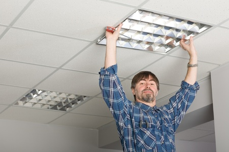 Electrician installs lighting to the ceiling in the office. Stock Photo