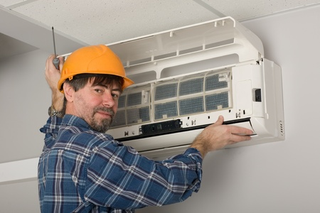 condicionador: Repairer conducts adjustment of the indoor unit air conditioner. Banco de Imagens