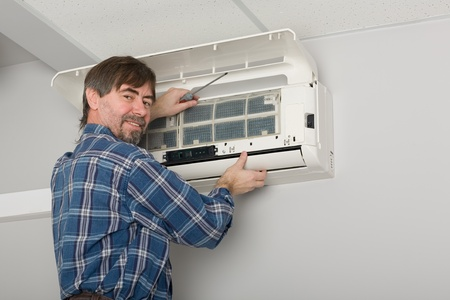 fettler: Repairer conducts adjustment of the indoor unit air conditioner. Stock Photo