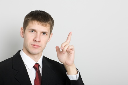 Young businessman points his hand towards the.  photo