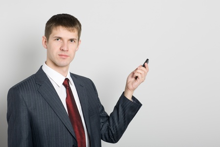 Young businessman points toward your mobile phone. Stock Photo