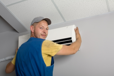 aire acondicionado: J�venes de instalaci�n instala hombre el acondicionador de aire nuevo en la Oficina.