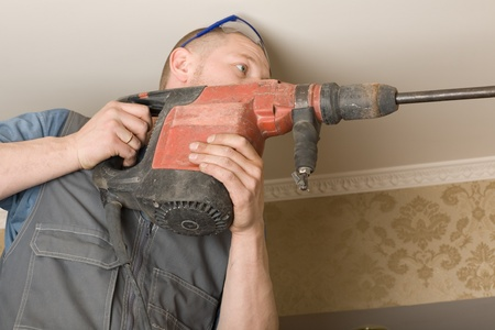 fixer: Technician air conditioning drills the wall. Work on installing a new air conditioner.