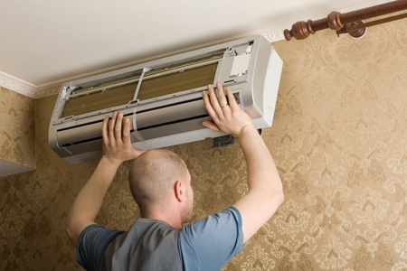 erector: Air conditioning technician installs a new air conditioner in the apartment. Stock Photo