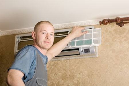 fettler: Adjuster air conditioning system sets a new air conditioner in the apartment. Stock Photo