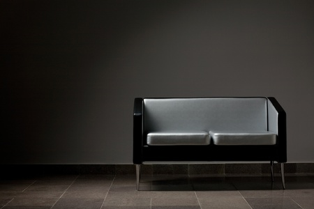 Modern lounge couch against a gray wall. Studio lighting. photo