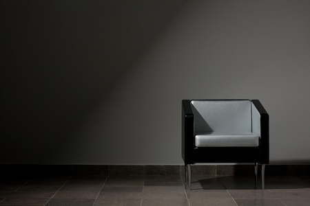 Modern lounge chair on a gray wall. Studio lighting. photo