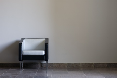 Modern lounge chair against a gray wall. Daylight.